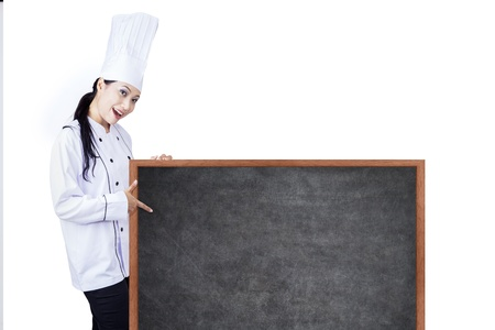 Beautiful Asian chef is holding a blank blackboard to show todays menu