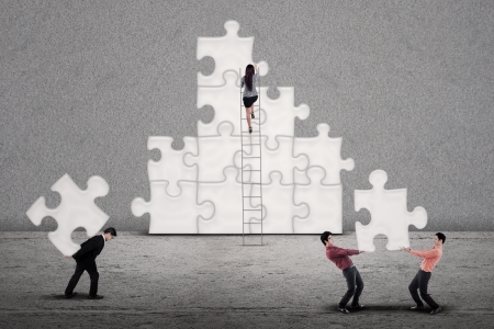 Business team building puzzles together on grey background