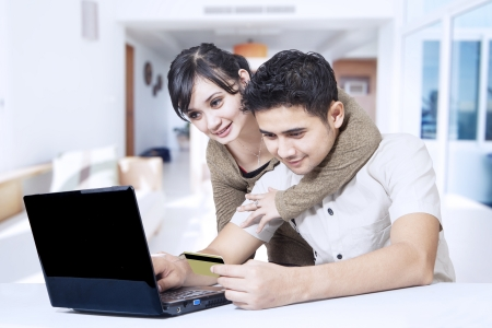 Happy couple doing  online shopping at home