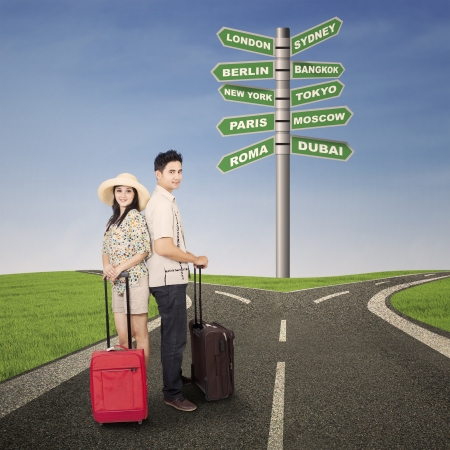 Photo for Couple honeymoon travel with luggages and road sign - Royalty Free Image