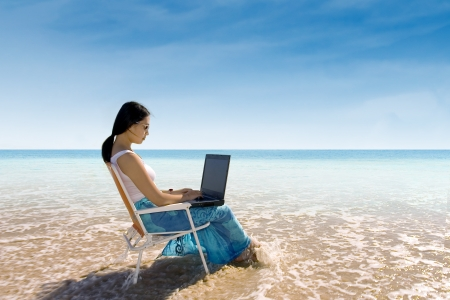Attractive woman working with laptop on the beach