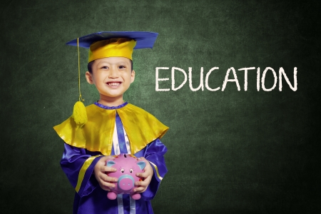 Happy scholar dressed toddler carrying a piggybank