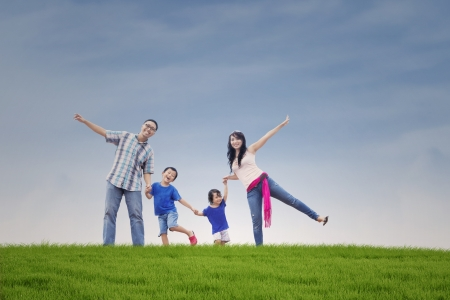 Happy Asian family on the green hillの写真素材