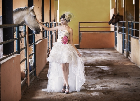 Beautiful bride touching a horse at the ranch