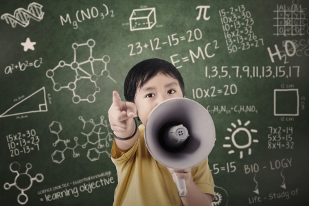 Boy with speaker at classroom with written formula and shapes