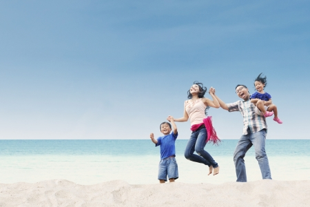 Cheerful family jumping at white sand beachの写真素材