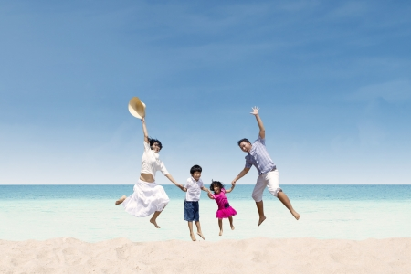 Happy family jumping at white sandy beach, Australia