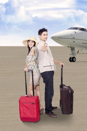 Asian couple is travelling by airplane, carry luggages at the airport