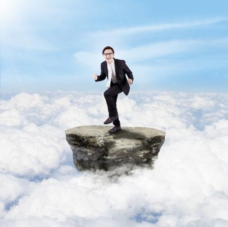 Photo pour Happy businessman dancing on a rock above clouds - image libre de droit