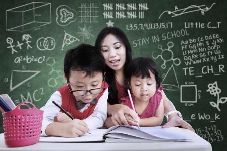 Beautiful teacher help children to write in classroom
