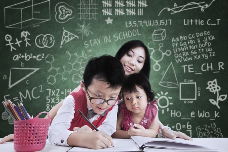 Asian sister and brother is learning to write in class with the teacher