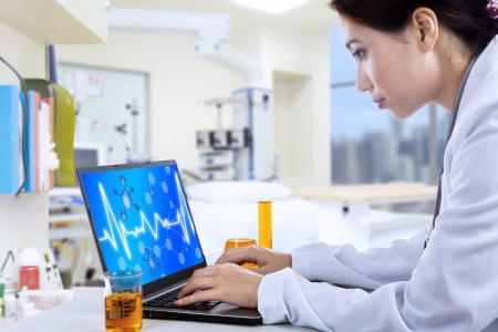 Attractive female doctor working with laptop in lab