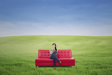 Pensive woman having coffee on red sofa at green field outdoor