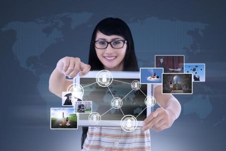 Photo pour Happy young female is showing a tablet with world map connection and pictures on blue - image libre de droit