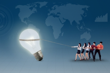 Business teamwork is pulling lit bulb on blue world map backgroundの写真素材