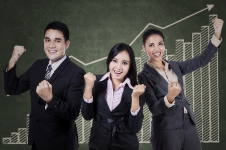 Successful business team celebrating their triumph with graph on chalkboard