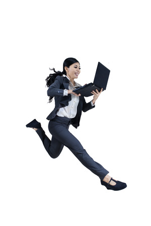 Excited woman running and holding a laptop on white background