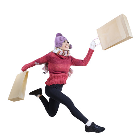 Winter woman running and holding shopping bags isolated on white background
