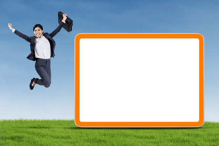 Photo pour Happy businesswoman is jumping with blank board on the meadow - image libre de droit