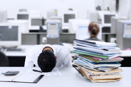 Foto de Tired young businessman is sleeping at desk in office - Imagen libre de derechos