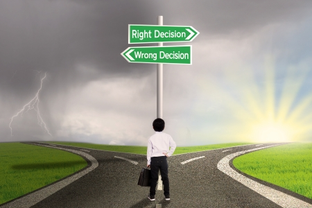 Little business child is standing on the road with a sign of right vs wrong decision