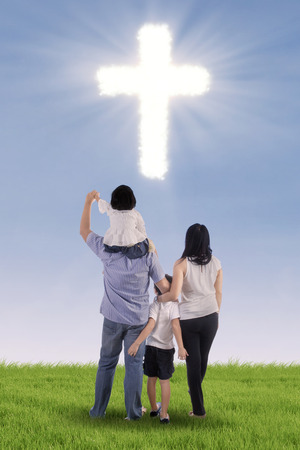 Christian family having fun on green field with cross symbol