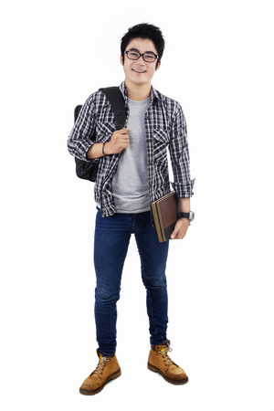 Male college student standing on white background