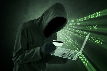 Internet theft concept - Man holding credit card with laptop on his hand