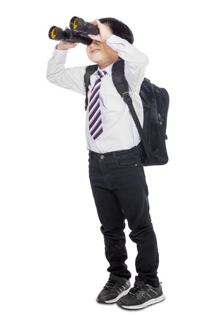 Little elementary school student using binoculars in studio, isolated over white