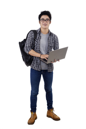 Photo pour Full length of male student carrying backpack and holding laptop computer in studio, isolated over white background - image libre de droit
