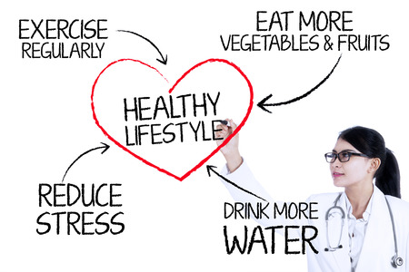 Foto de Female doctor drawing healthy lifestyle concept with marker on glass wall - Imagen libre de derechos