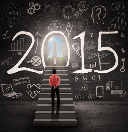 Photo pour Young businessman standing on the stairway and look a door to success in 2015 - image libre de droit