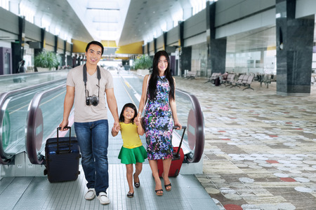 Portrait of asian family carrying luggage and walking in the airport hall for holiday