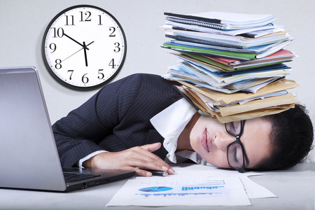 Portrait of indian entrepreneur sleeping in the office with paperwork over her head