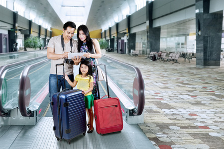 Foto de Asian family doing holiday trip and looking a map on the digital tablet at the airport hall - Imagen libre de derechos