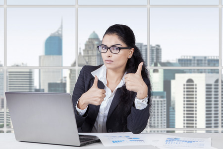 Successful indian businesswoman showing thumbs up in the office while working with laptop