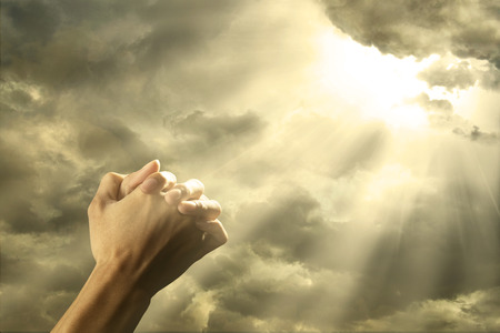 Closeup of prayer raised hands on the sky with bright rays from the cloud