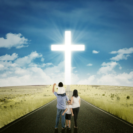 Back view of two parents standing on the road with their children looking at a cross