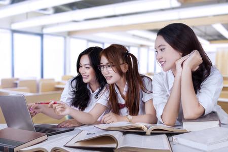 Foto de Portrait of lovely three female high school student, studying together in the classroom - Imagen libre de derechos