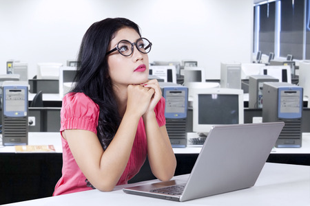 Portrait of female worker sitting in the office with laptop computer on the table and looks thinking something