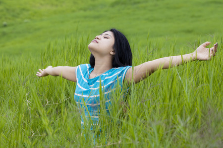 Beautiful young woman with casual clothes enjoying freedom while breathe fresh air and outstretched hands on the meadow