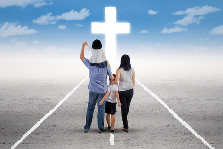 Back view of little happy family standing on the road and follow a cross