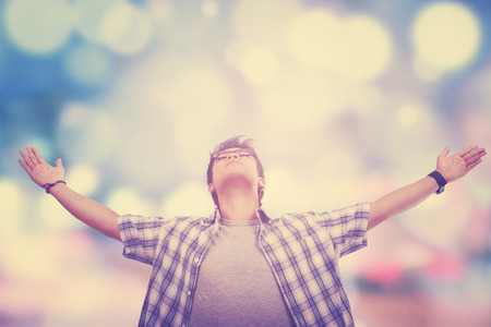 Portrait of young man enjoy freedom and raised hands, shot with defocused background