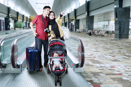 Portrait of two parents holiday together with their baby on the pram and standing in the airport hall