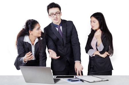 Portrait of three multi ethnic businesspeople in discussion and debating with laptop, isolated on white