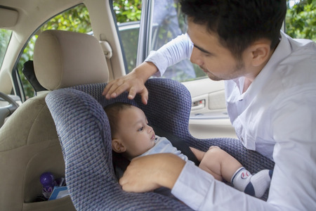 Portrait of young man putting his newborn baby on the car seat