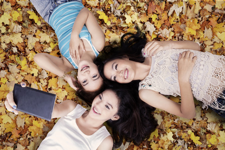Unique perspective of three teenage girls taking picture with smartphone while lying down on autumn leavesの写真素材