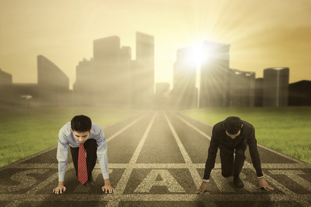 Business competition concept with two businessman kneeling on the start line and ready to compete