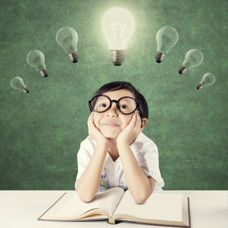 Photo pour Attractive female elementary school student with a textbook on the table, thinking idea while looking up at bright light bulb - image libre de droit