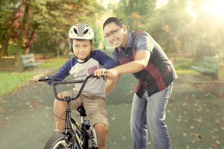Photo for Portrait of young father teaching his son to learn how to ride a bicycle on the road at the park - Royalty Free Image